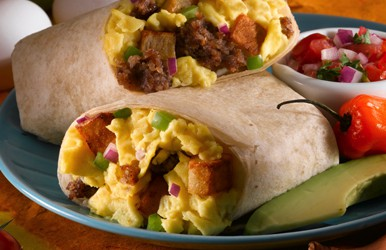 A burrito consisting of eggs, sausage and bell peppers sitting on a blue plate