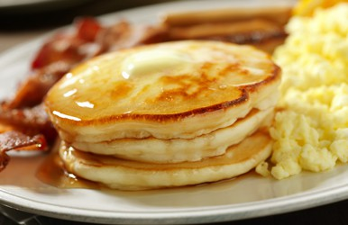 A stack of pancakes with syrup and bacon