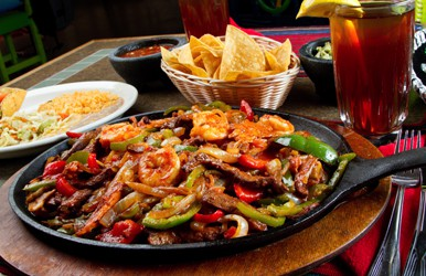 A plate of fajitas with a basket of chips, guacamole and salsa.